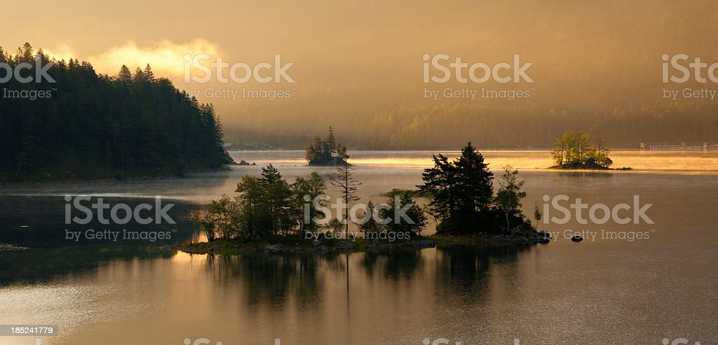 Small Islands in Lake Eibsee against Mount Zugspitz at Sunrise stock photo