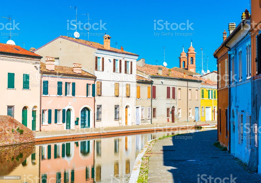 Small Italian town Comacchio also known as 'The Little Venice', Emilia Romagna region, province of Ferrara, Italy: Colored houses in traditional architectural style and canal for boats near them stock photo