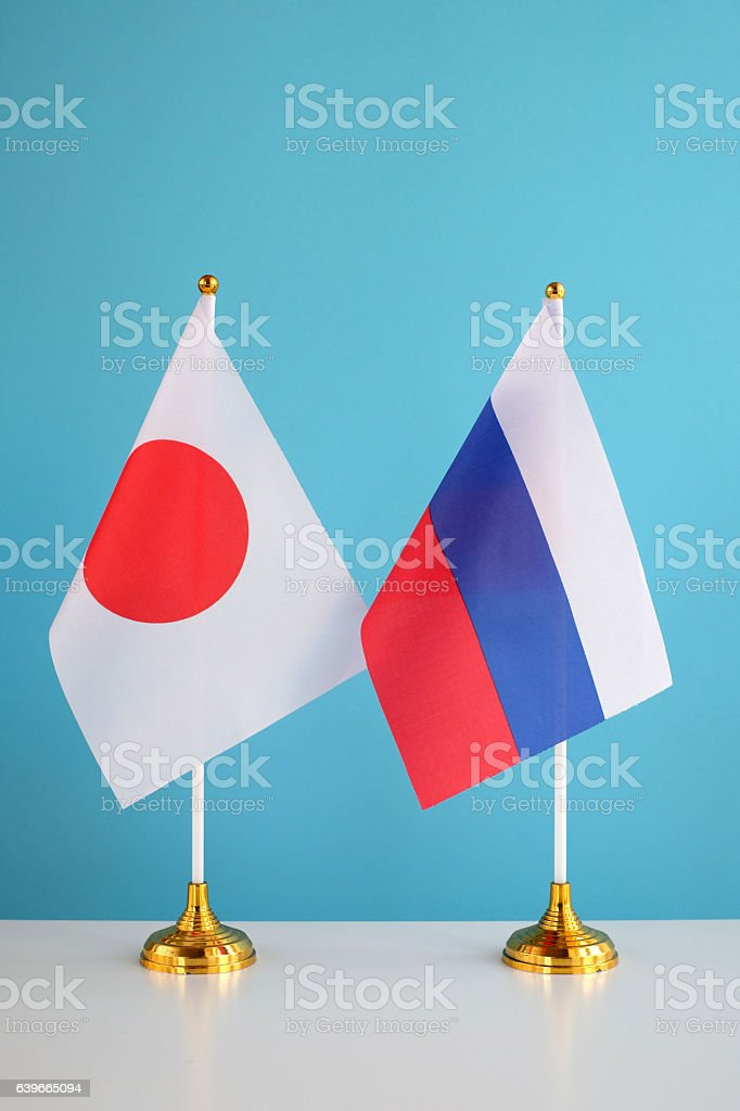 Small Japanese and Russian Flags on table stock photo