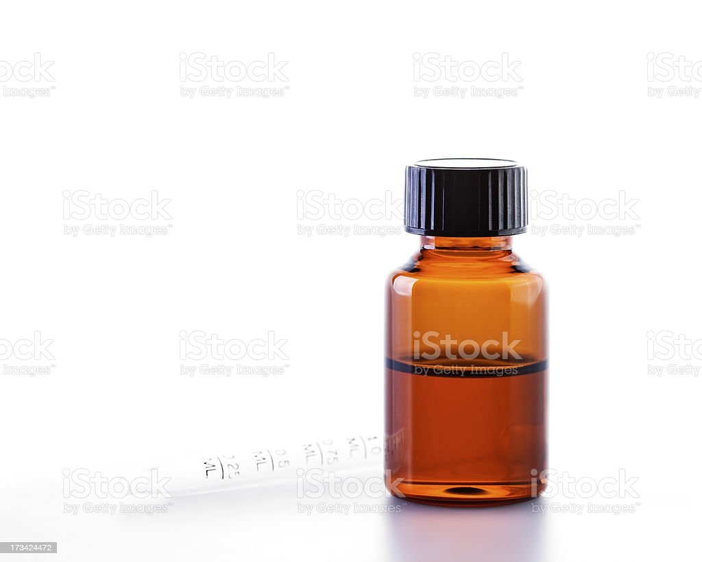 Small jar of essential oil with a dropper in the background stock photo