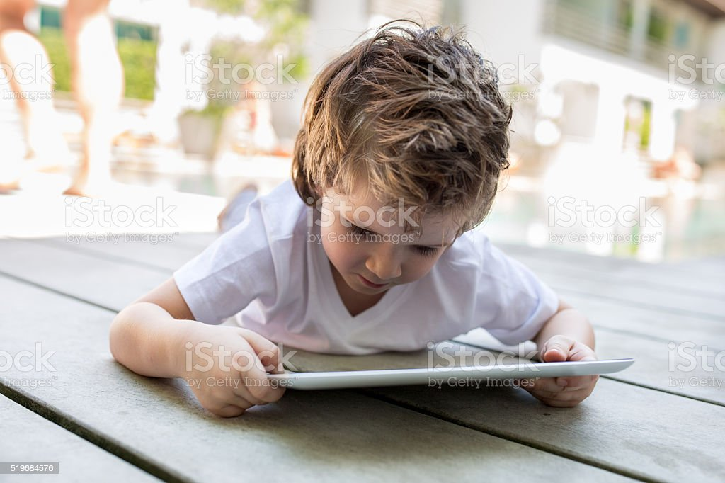 Small kid using digital tablet on the floor. stock photo