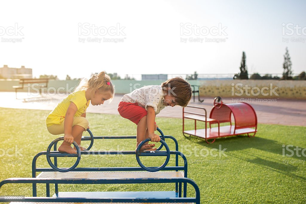 Small kids playing on the playground at the park. stock photo