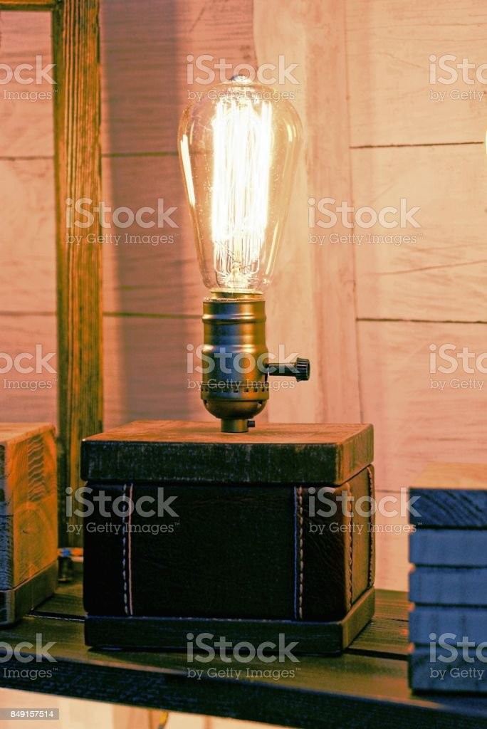 A small lamp with a bright lamp near a wooden wall stock photo