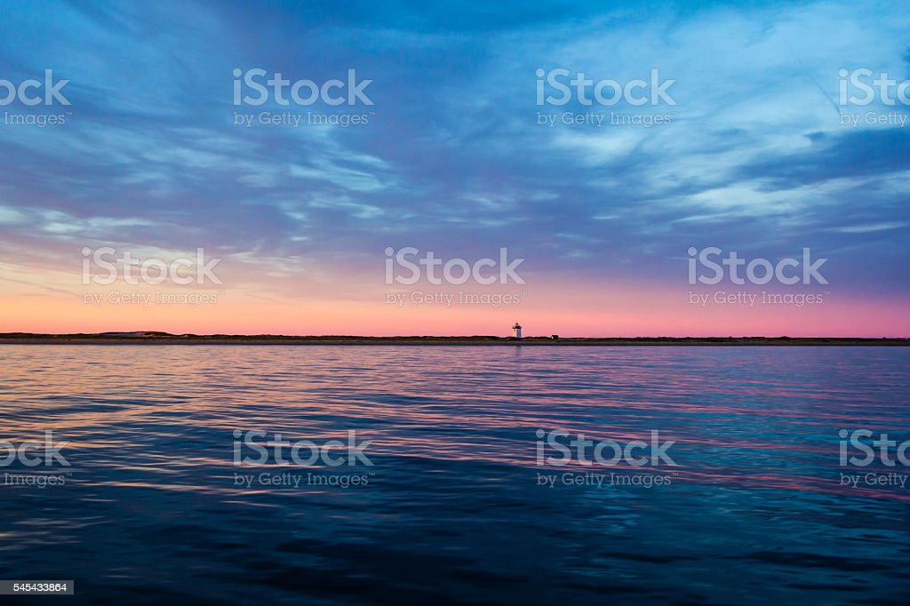 Small lighthouse at dusk sunset stock photo