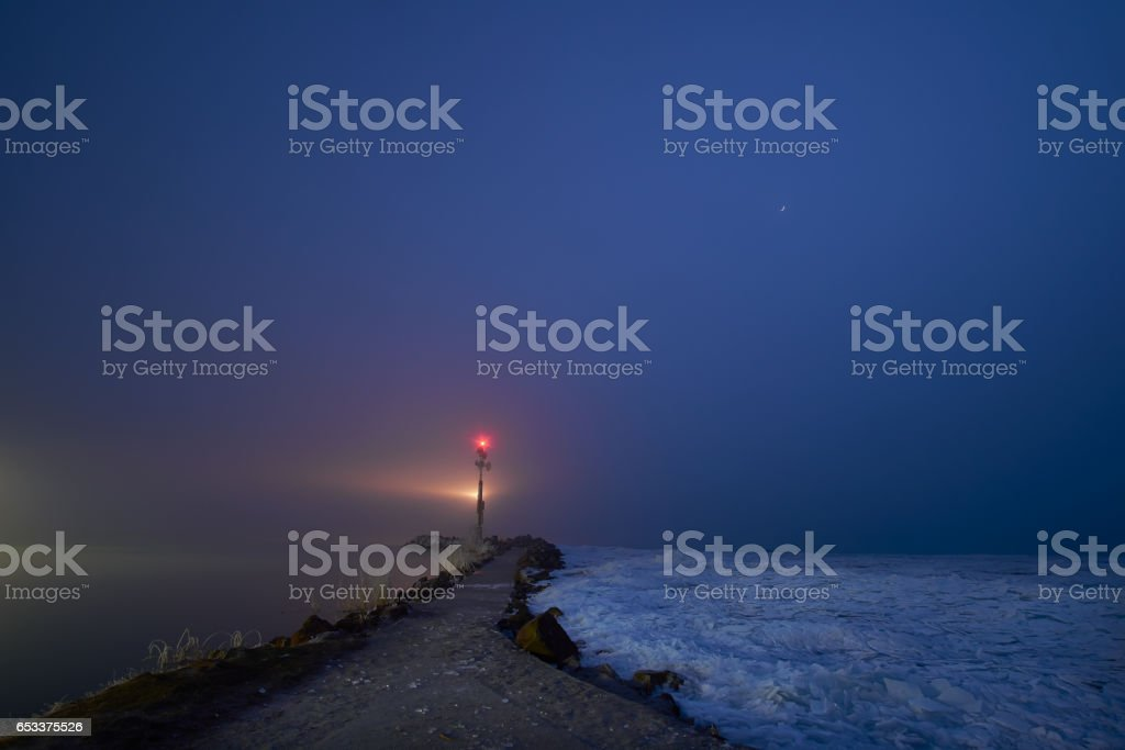 Small lighthouse in the lake at night stock photo
