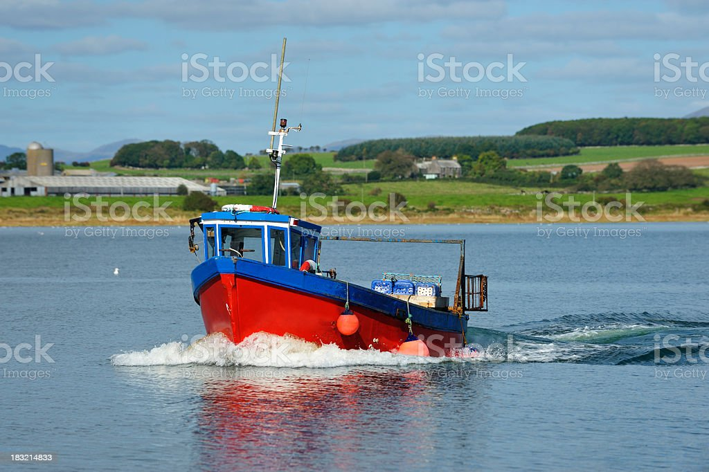 Small lobster boat coming into a Scottish harbour stock photo