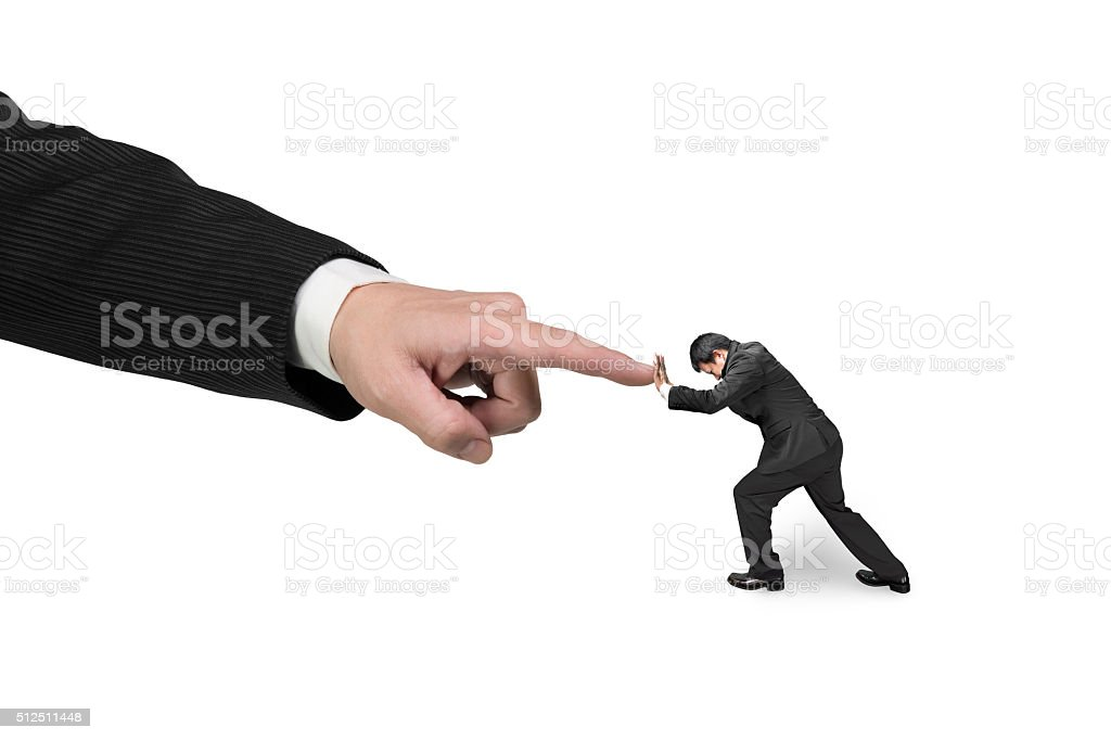 Small man pushing against big other hand forefinger stock photo