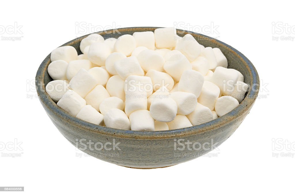 Small marshmallows in an old stoneware bowl stock photo