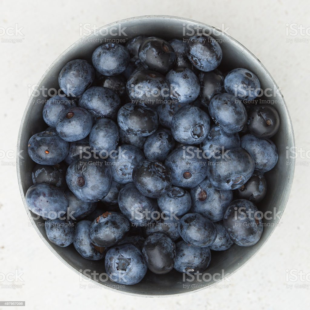 Small metal bowl of fresh blueberries stock photo