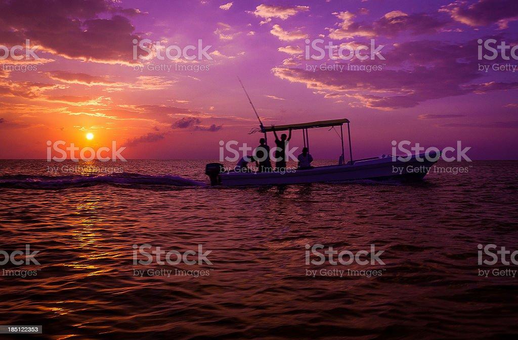 small motor boat at sunset stock photo