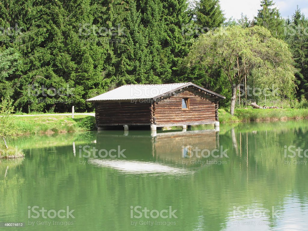 Small mountain lake with house over water and forest background stock photo