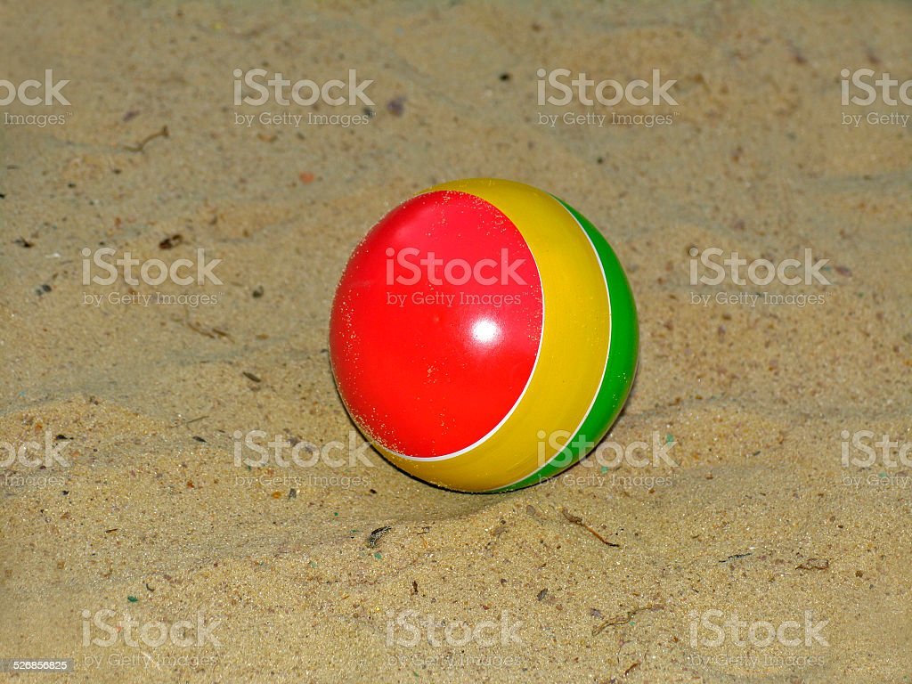 Small multi-colored children's ball on sand stock photo