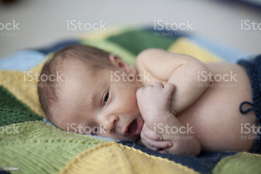 Small newborn baby laying on quilt stock photo
