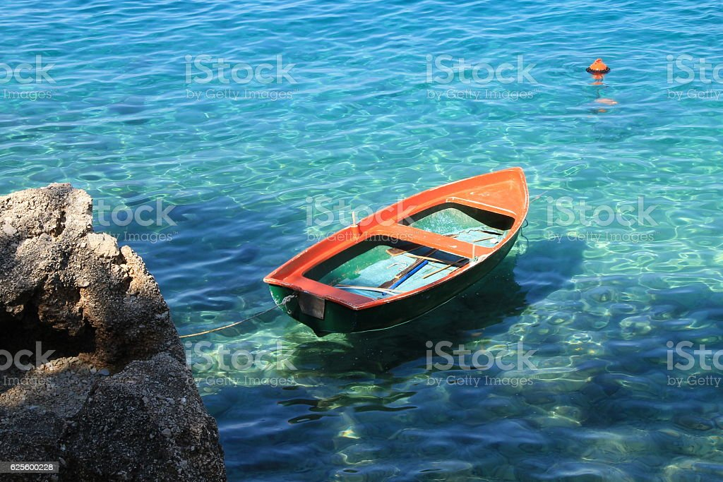 Small orange boat in Adriatic sea , Croatia moments stock photo