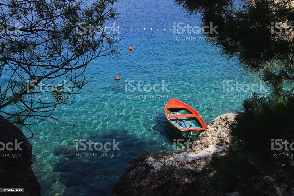 Small orange boat in Adriatic sea in Brela , Croatia stock photo
