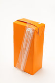 small orange drinks carton with straw