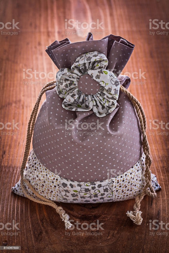 small ornated bag with strings on old wooden board stock photo