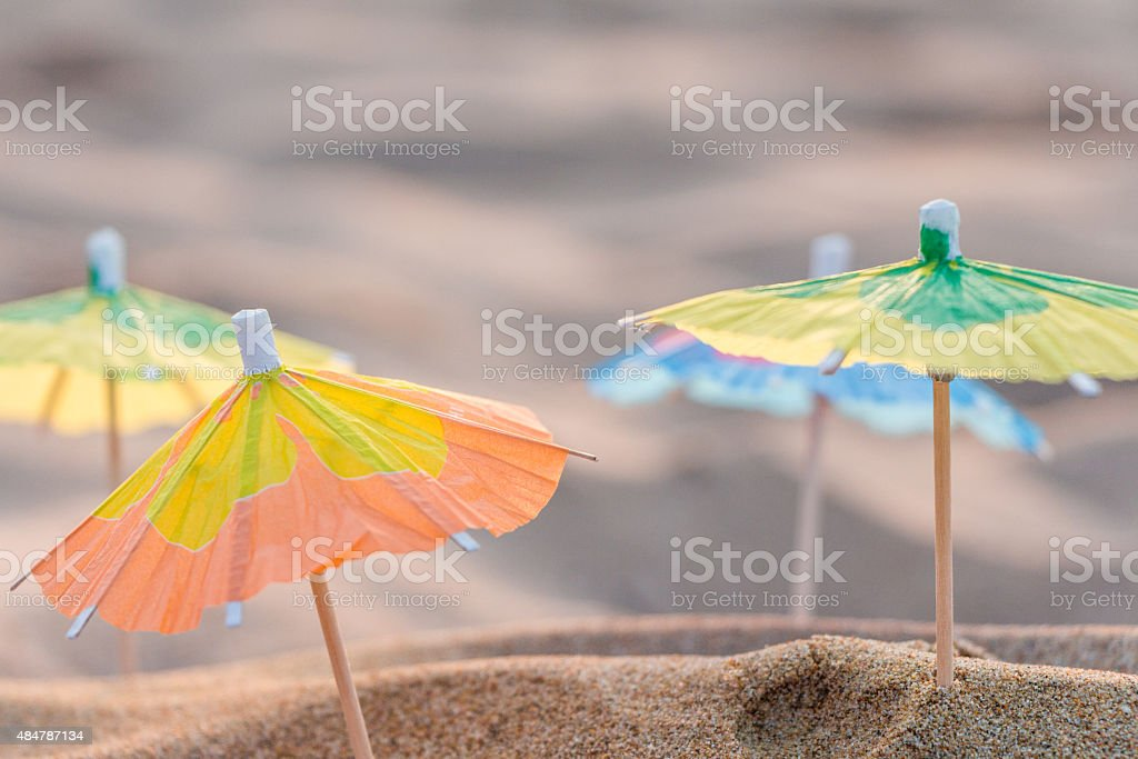 Small paper umbrellas on the beach stock photo