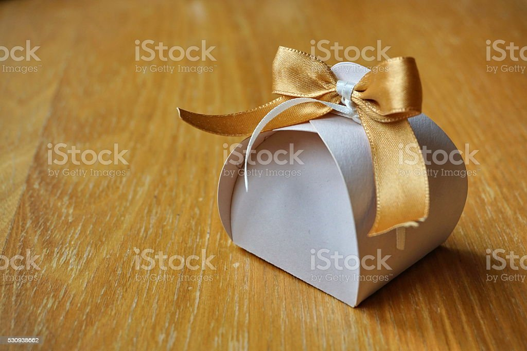 Small papery gift box with golden ribbon on the top stock photo