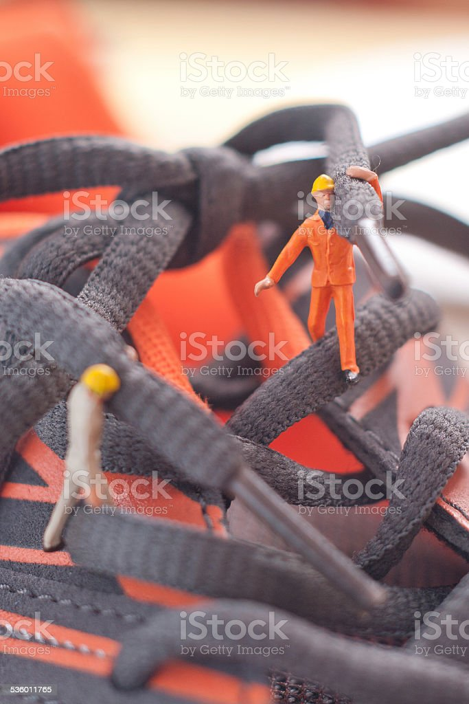 Small people associated shoe. The concept of teamwork stock photo