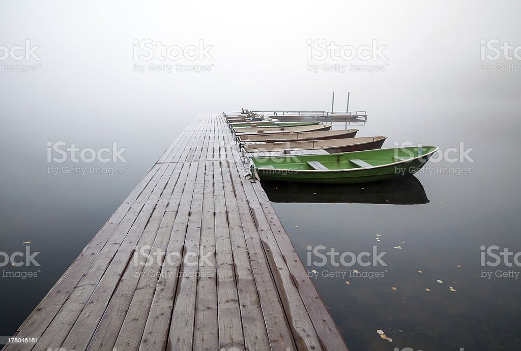 Small pier with boats on lake in foggy morning royalty-free stock photo