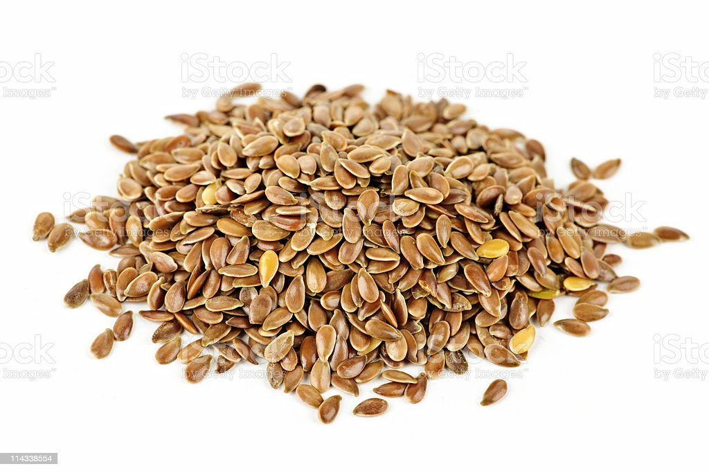 A small pile of brown flax seed on a white background stock photo