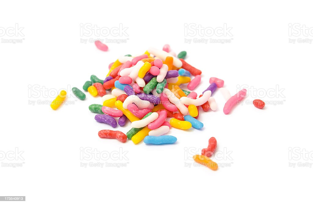 Small pile of rainbow sprinkles on white backdrop stock photo