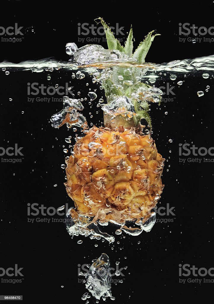 Small pineapple falling in water on black royalty-free stock photo