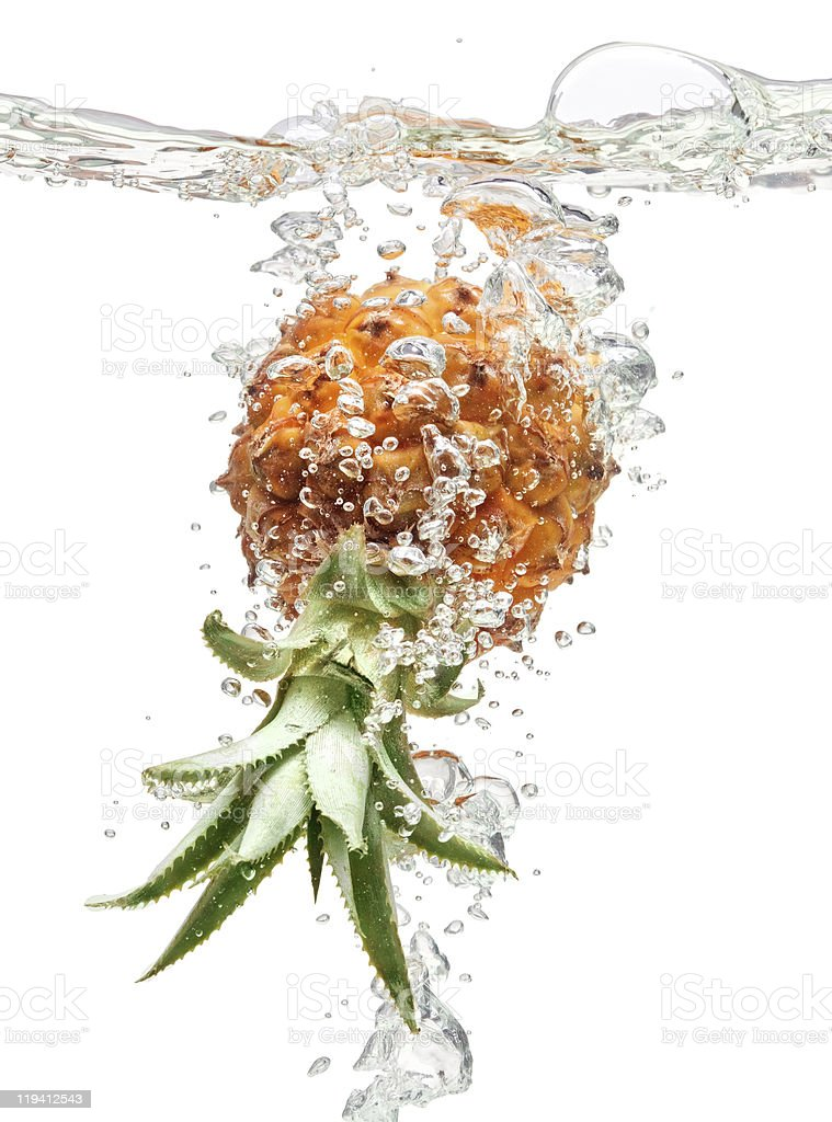 Small pineapple falling in water on white royalty-free stock photo