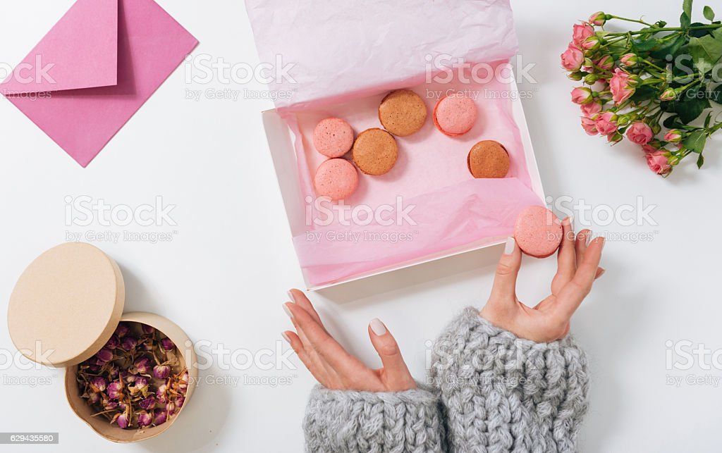 Small pink macaroon being in hands of a woman stock photo
