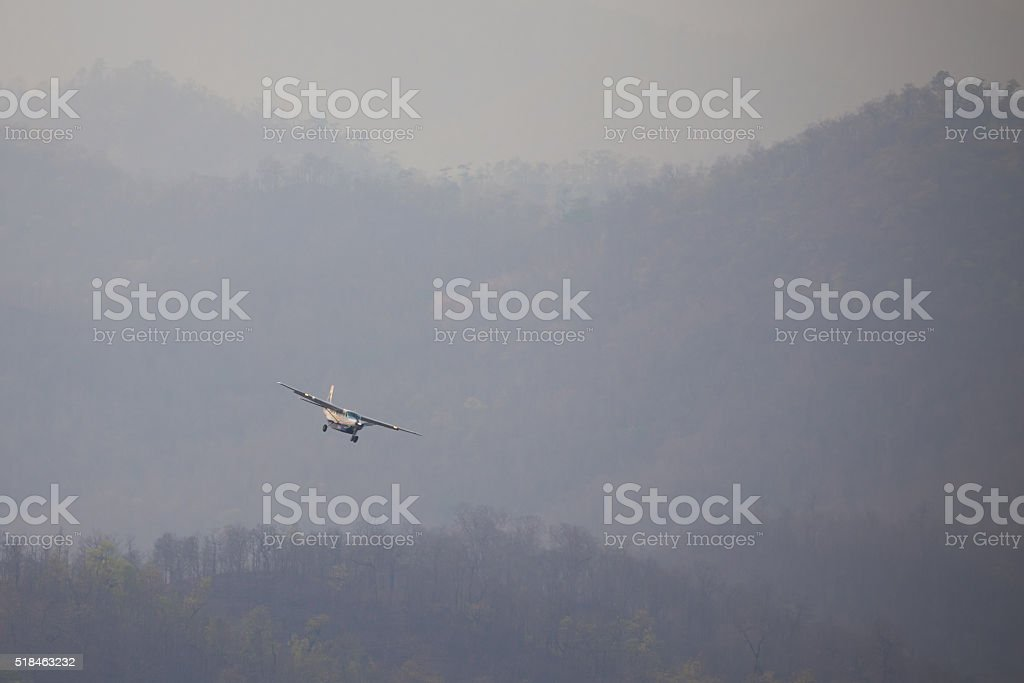 Small plane flew through  the burning forests stock photo