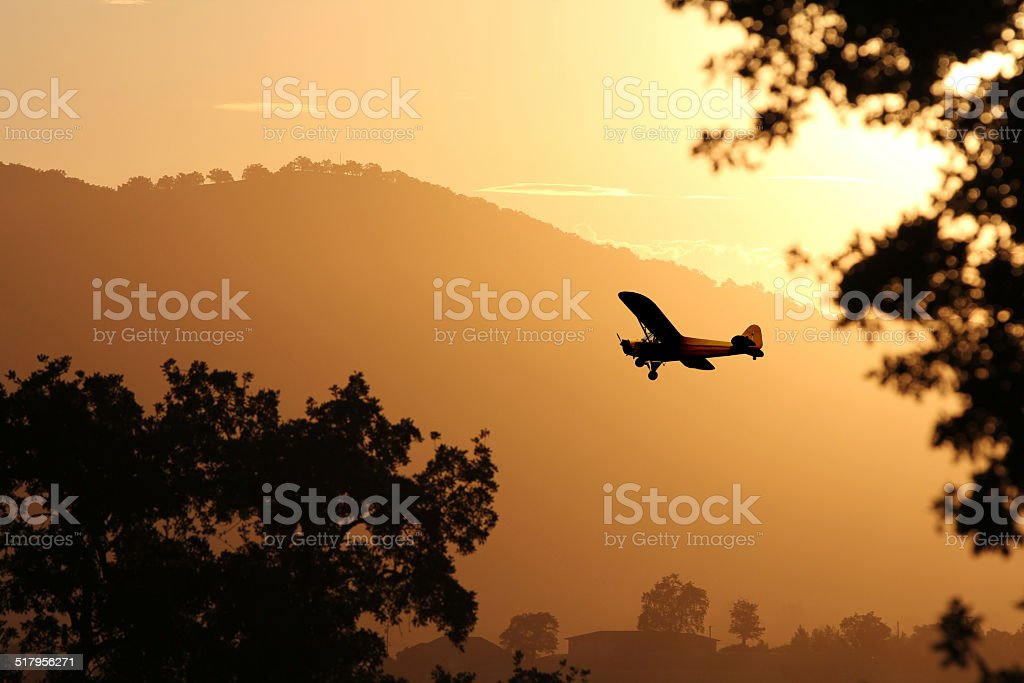 Small plane flying at sunset. stock photo