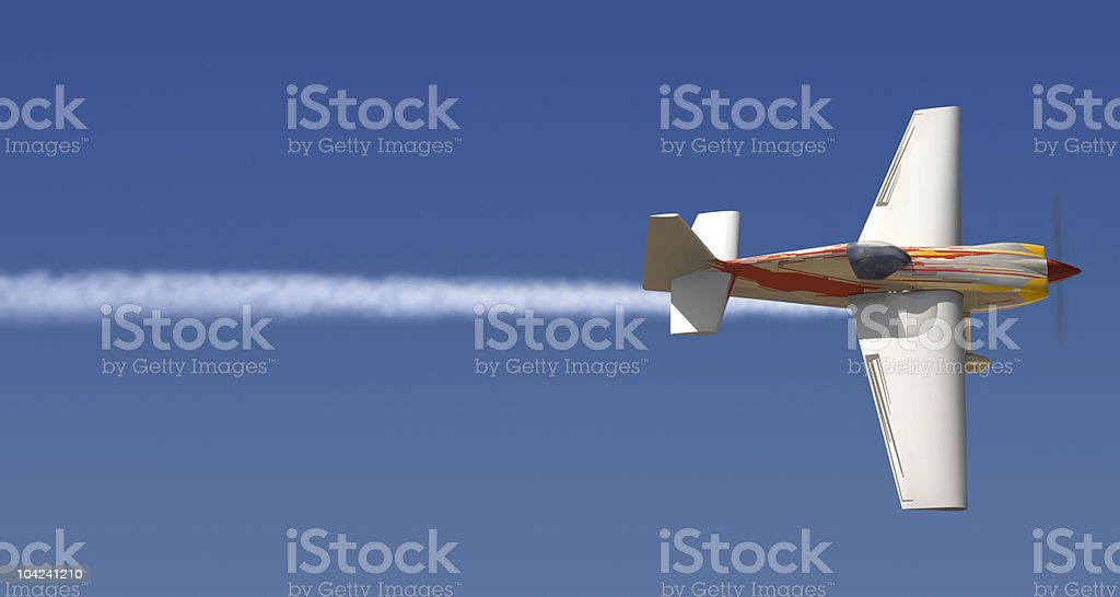 A small plane in mid flight writing a line through the sky royalty-free stock photo