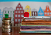 Small plastic house model on top of stacked coins