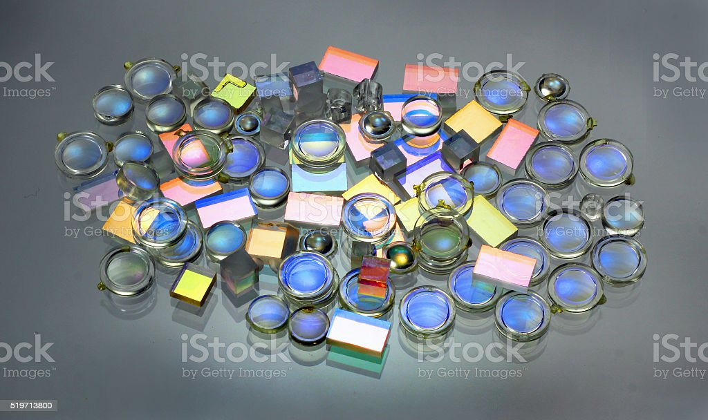 Small plastic lenses semitransparent mirrors and prisms on glass stock photo