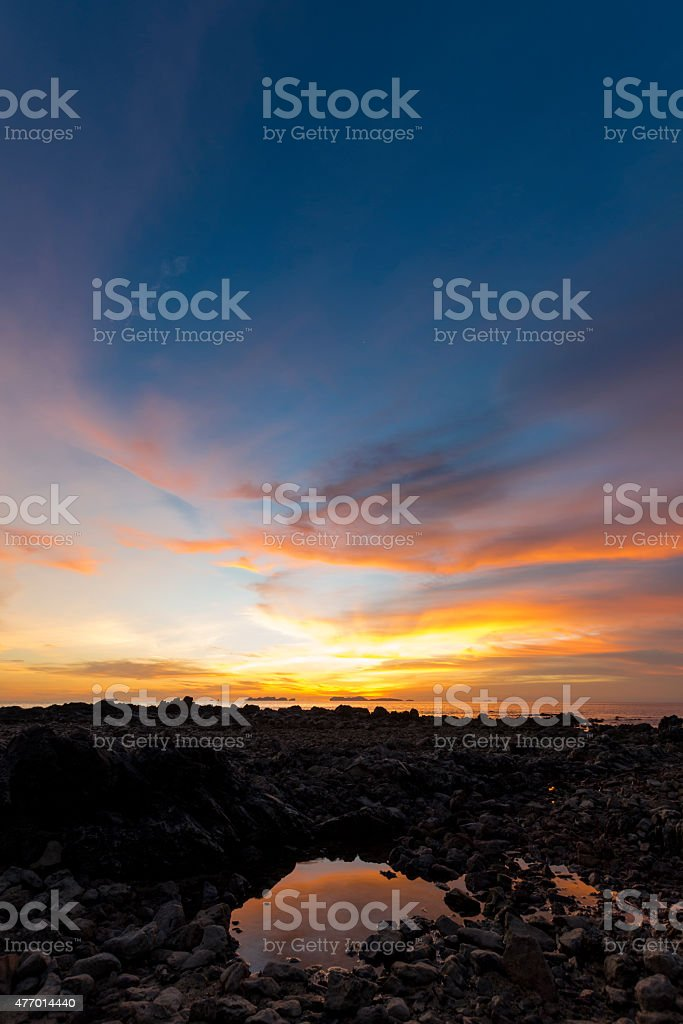 Small pond on rocky beach at sunset. stock photo