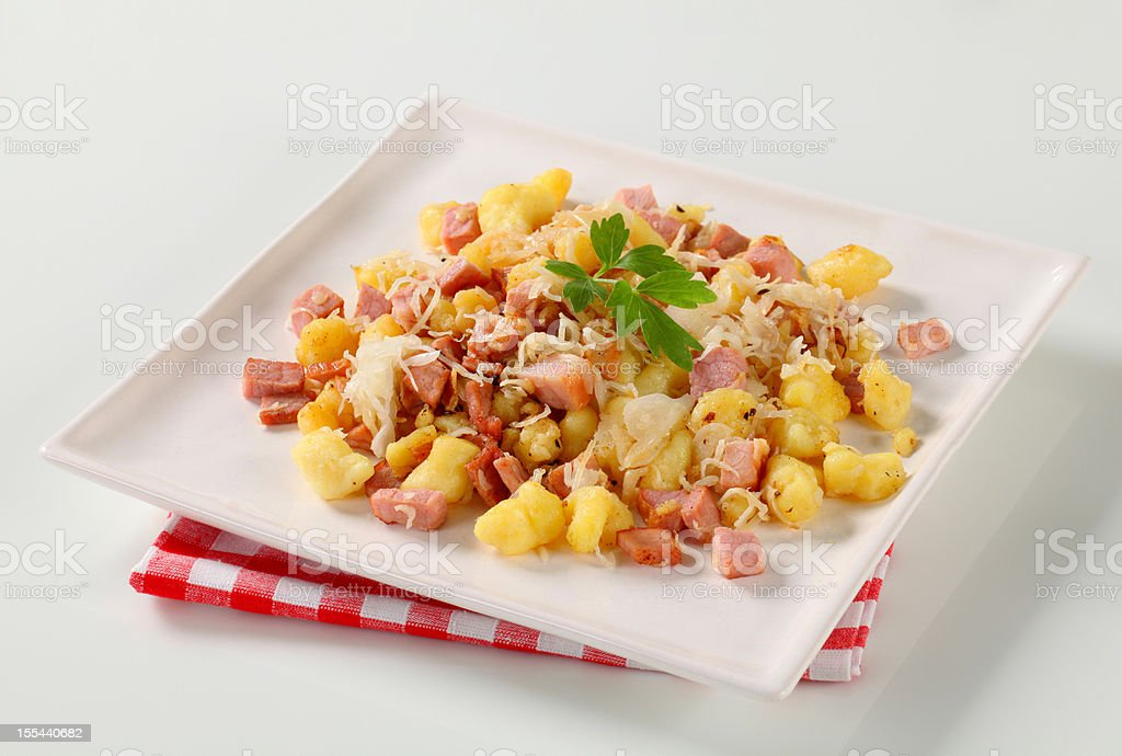 Small potato dumplings with diced ham and white cabbage stock photo