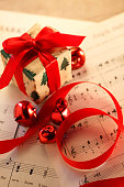 Small Present Resting On Christmas Sheet Music