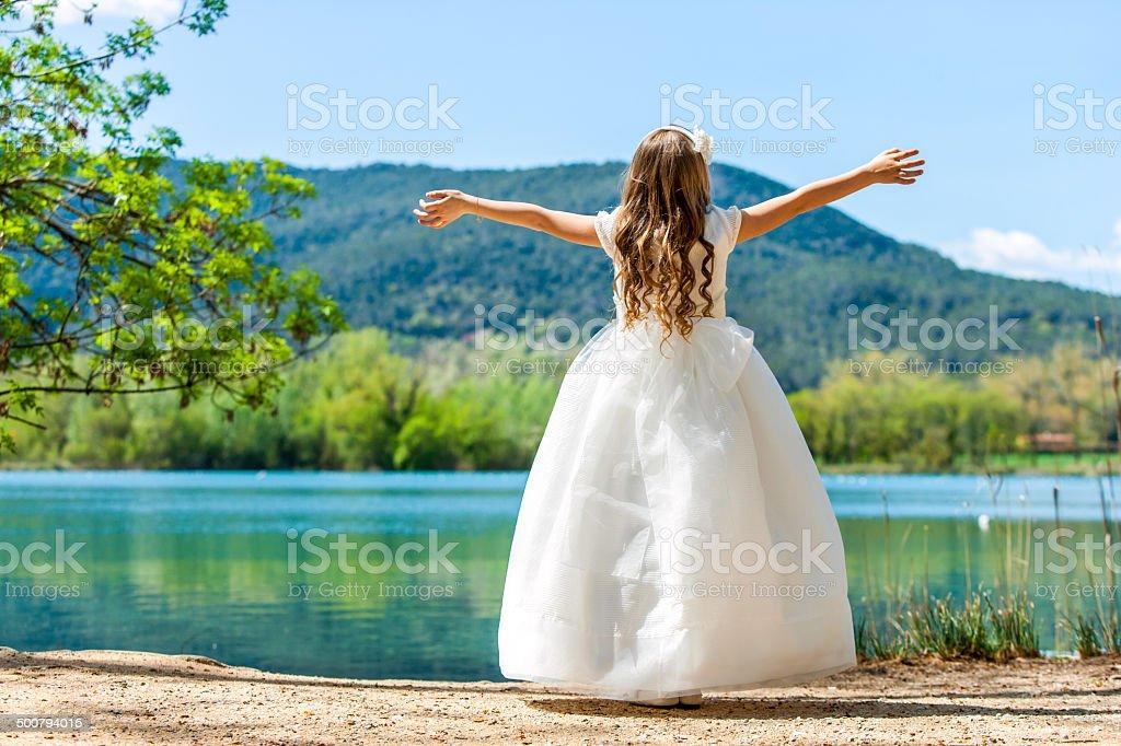 Small princess in white dress at lake. stock photo