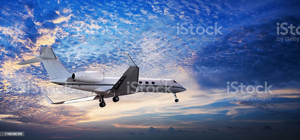 Small private jet in a sunset sky stock photo