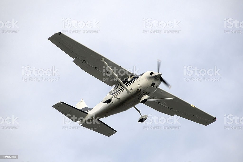 Small private plane flying against the sky stock photo