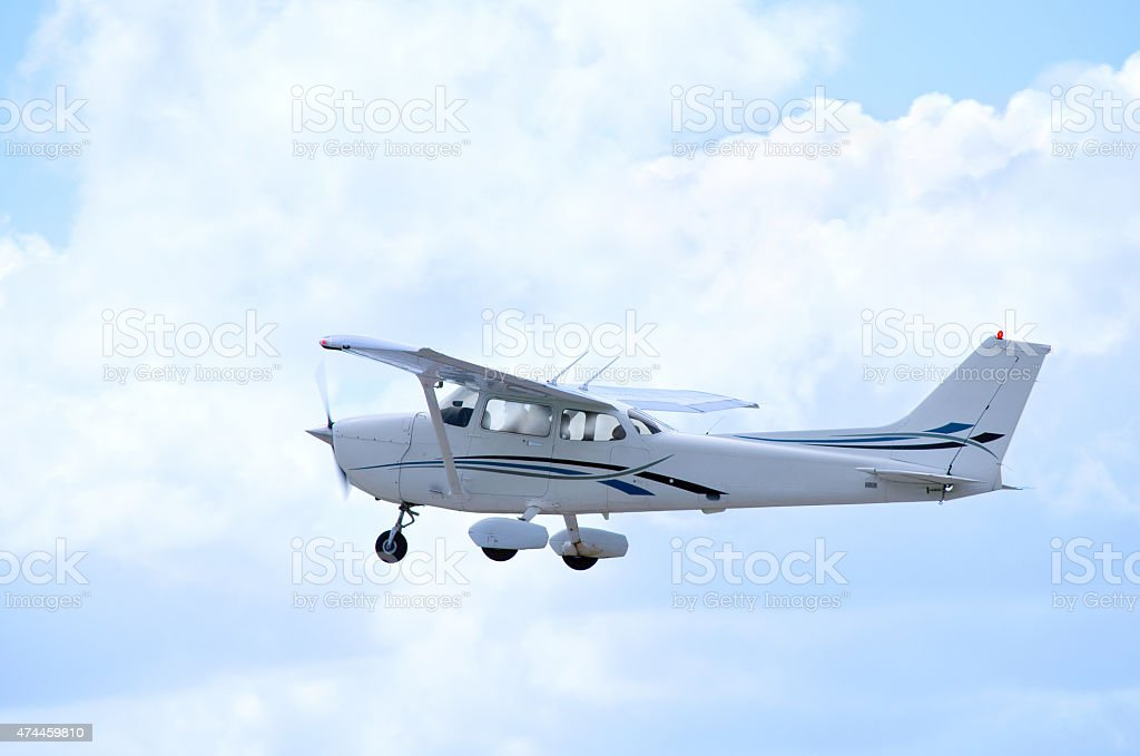 Small private single engine airplane in flight with clouds stock photo
