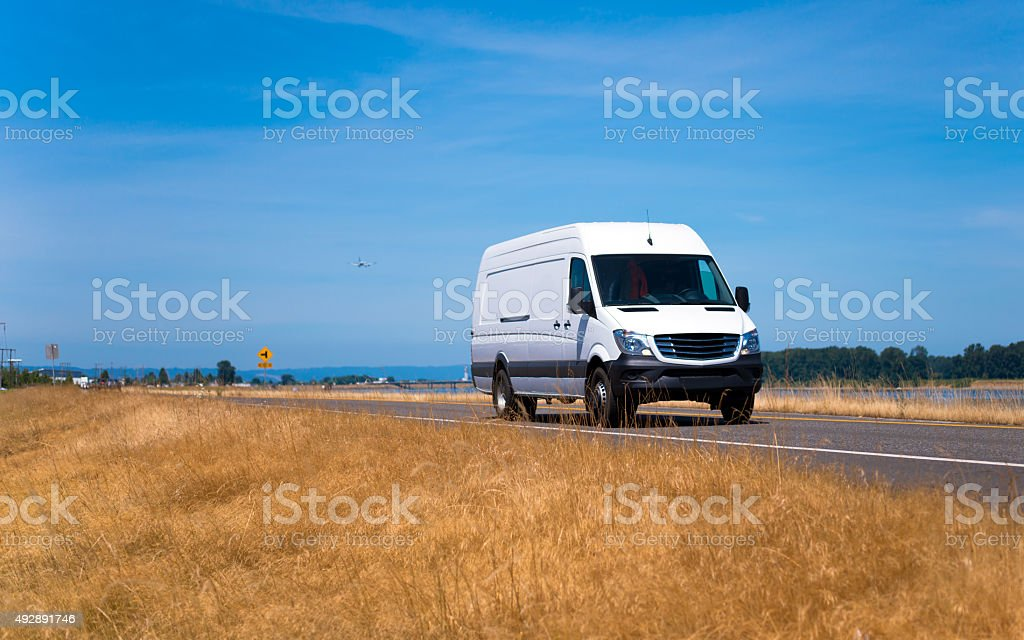 Small pro commercial cargo mini van on spectacular road stock photo