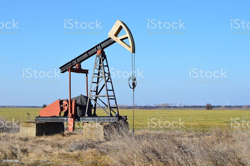 Small Pumpjack in the green fields near Sabla, Bulgaria stock photo