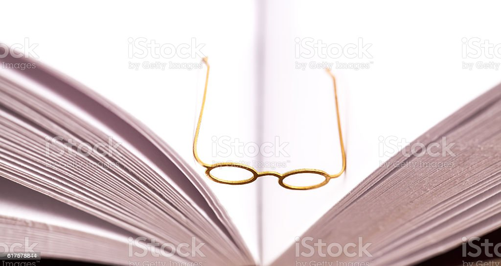 Small reading glasses on open book stock photo