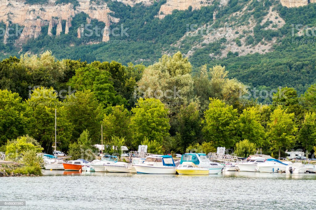 Small recreational group of boats at deck in small pier french marina bay harbor with trees and mountain in background on Rhone river in France stock photo