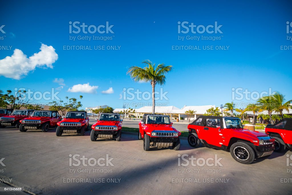 Small red electric Hummers awaiting tourists, Grand Turk stock photo