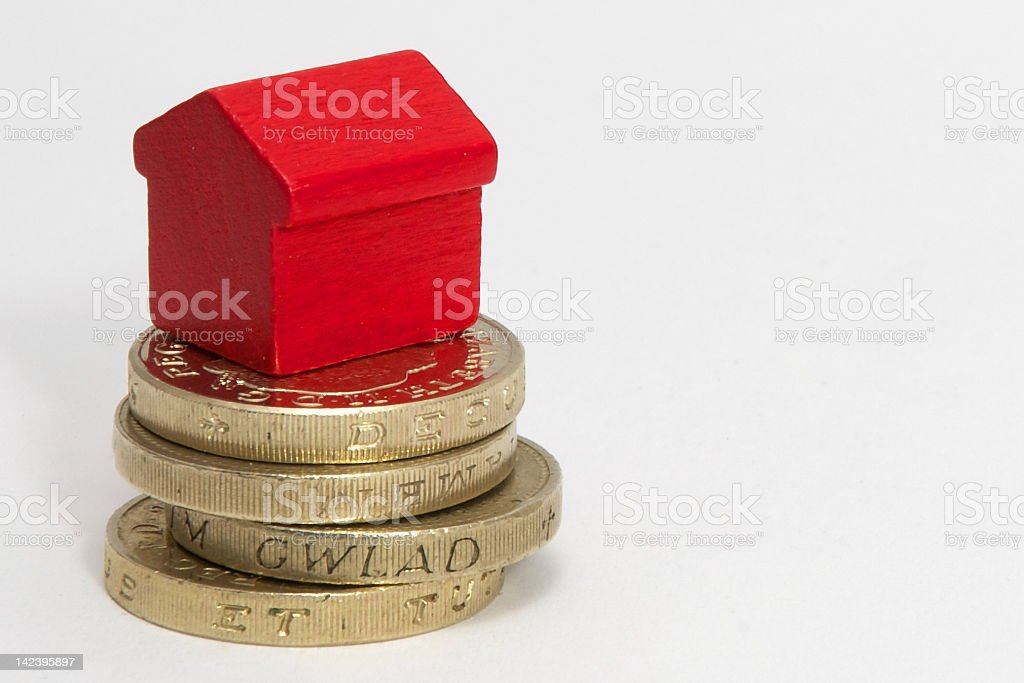 A small red house setting on top of a stack of gold coins stock photo
