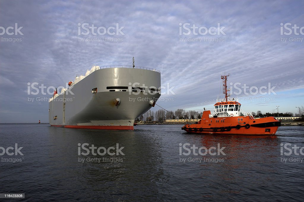 A small red ship against a larger ship stock photo