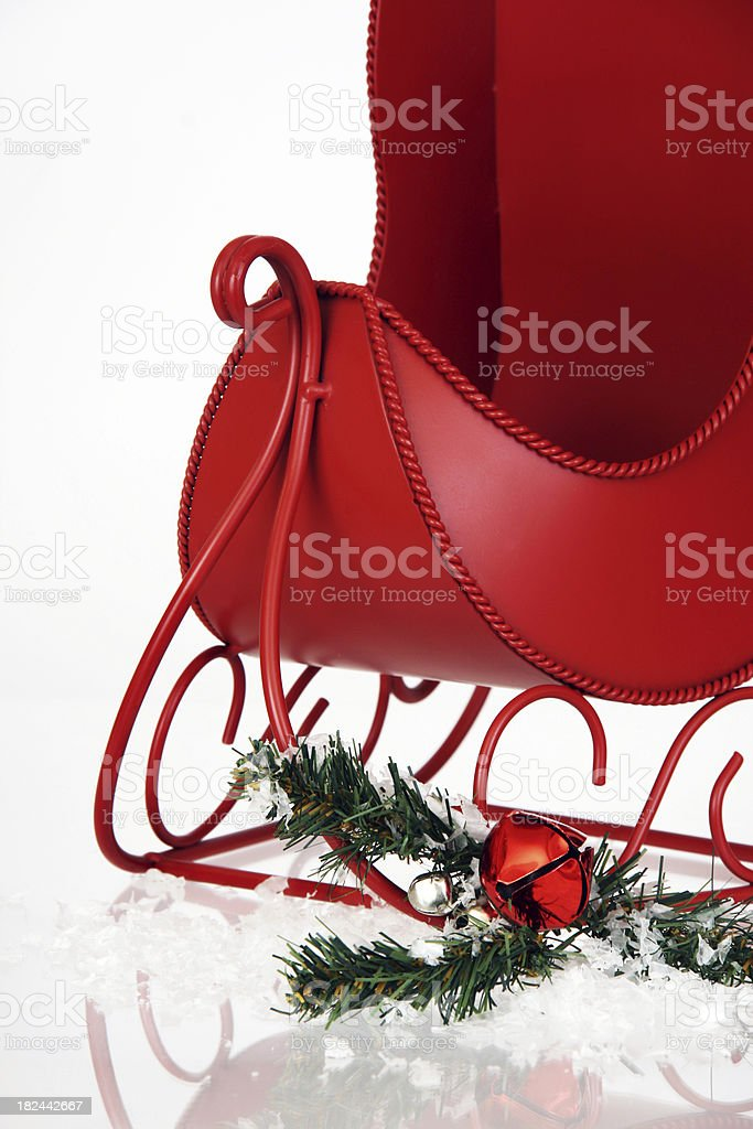 Small red sleigh, bells, evergreen, snow. Copy space. Vertical. stock photo